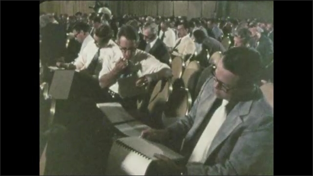 1960s: UNITED STATES: man notes charts on wall. People attend meeting. Man at podium. Lease sale meeting