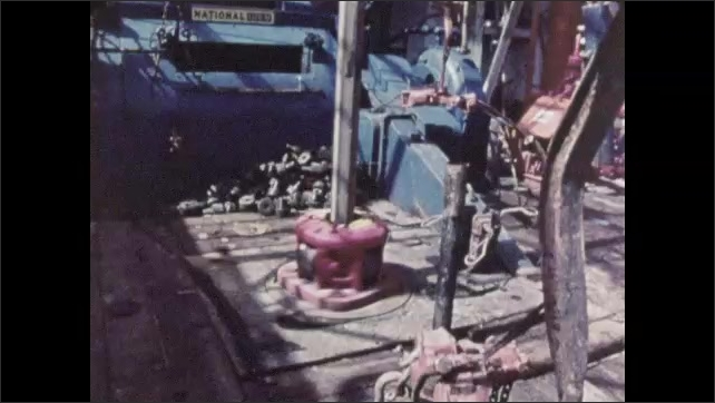 1960s: UNITED STATES: man in hard hat on rig. Men set up drill. Drilling of exploratory well. Charts and stars.