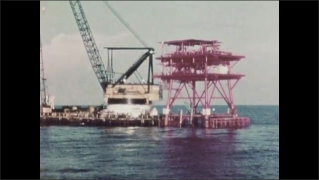 1960s: UNITED STATES: building of rig and platform. Permanent drilling well. View across pipeline and platform