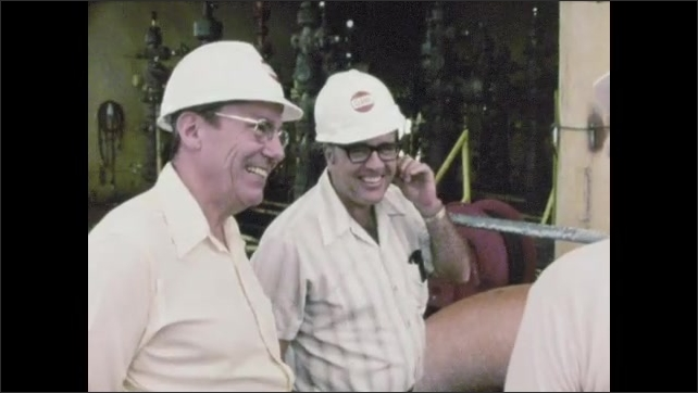 1960s: UNITED STATES: discovery of oil reserves. Men stand by pipes on rig. Men in hard hats.