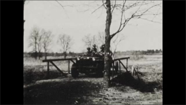 1940s: Soldiers on motorcycles, tanks, jeeps and horses ride down roads. Soldiers drop off howitzer cannon from jeep. Soldiers position cannon.