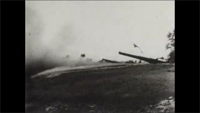 1940s: Camouflaged soldiers run across field. Soldier throws grenade into bunker. Men aim large artillery cannon. Men fire artillery. Men load shells into cannon. Large cannons fire.
