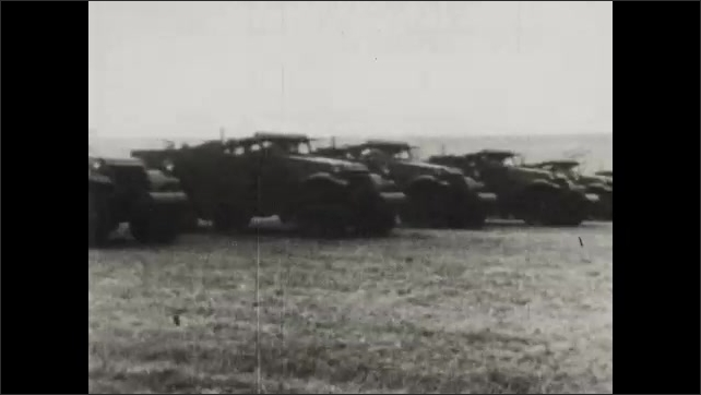 1940s: Men fire artillery guns behind sand bags. Dozens of trucks drive across field. Trucks carry soldiers and howitzers across field.