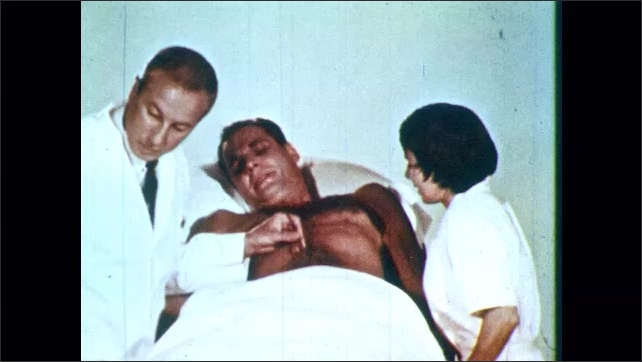 1960s: Male patient writhes in pain as doctor works on a wound and nurse holds him down. Doctor uses forceps and a swab.
