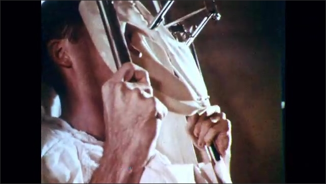 1960s: Child lights match and throws it on BBQ. Nurses around hospital bed. Woman writhes in pain. Needles and blood drips. Medical equipment and procedures. Patients in pain and being gassed.