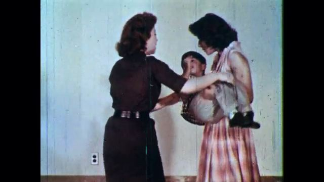1960s: Woman carry small boy into hospital. Women speak hurriedly to nurse. Nurse tries to calm women. Nurse looks down and thinks to self. Nurse looks at women.