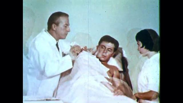 1960's: Male patient winces but stays still under sheet as doctor treats a wound. Nurse speaks to him and patient replies through clenched teeth.