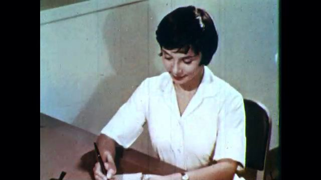 1960s: Nurse writes notes in a notebook and checks her watch.