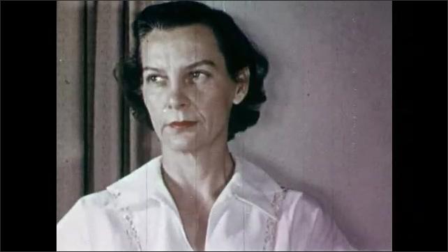 1950s: Hand paints shadows into collar of woman's portrait. Woman poses for portrait. Man studies woman, smiles.