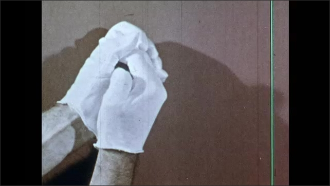 1950s: UNITED STATES: White gloved hands against background. Shadows on gloved hands. D Lighting example