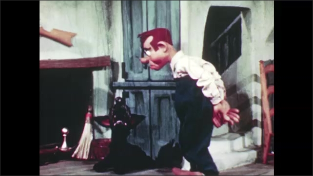 1950s: Devil and angel puppets hang in air. Marionette man puppet walks away from telephone, towards dog and fireplace. Puppet walks back to phone, picks up telephone receiver, sits down, listens.
