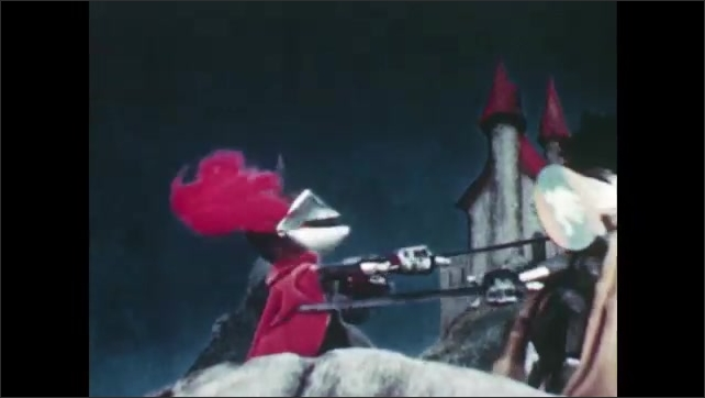 1950s: Puppet knights sword fight on top of bridge. Puppet slashes at other puppet's neck with sword. Puppet gets sword stuck in visor of other puppet's helmet.