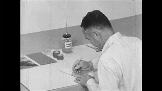 1960s: Man at drafting table takes piece of cardboard with glass frame laying over it, removes glass, places triangle on it, draws line then punctures two holes along line.