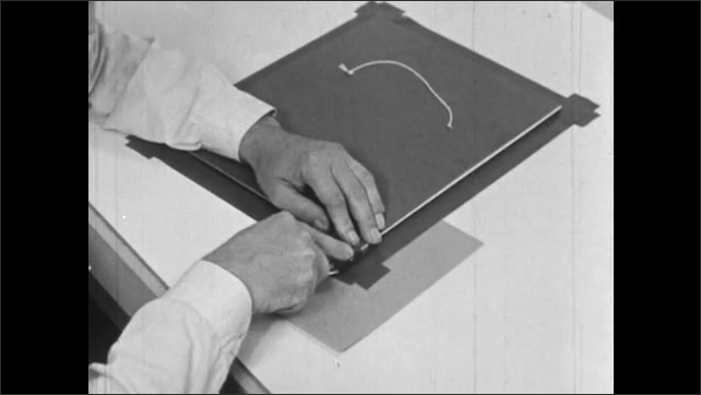 1960s: Man cuts excess pieces of tape from off edges around piece of cardboard.