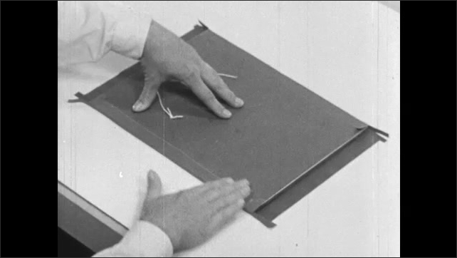 1960s: Man rotates cardboard frame with tape lining sides and folds tape in over cardboard.