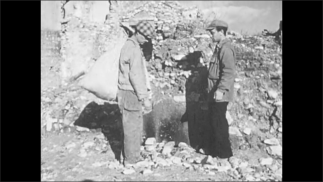 1940s: UNITED STATES: men stand by stone wall. Stones on ground. Man pushes rocks around with foot