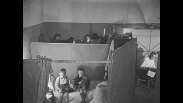 1940s: UNITED STATES: Man with beard and glasses. Catholic and Protestant displaced persons wait for repatriation. Family in cubicle. Lady sews with children