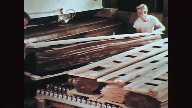 1970s: Two men stack slices of wood veneer in a sawmill.