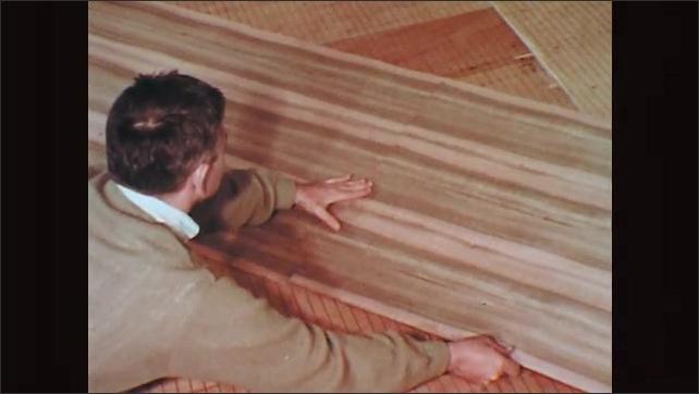 1970s: Man matches up grain in slices of wood veneer on workshop table. Hands join cut pieces of wood veneer.