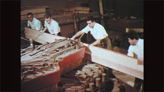 1970s: Wood panel slides out from under mechanical rollers. Men bend wood plank around grand piano form, clamping it in to place.