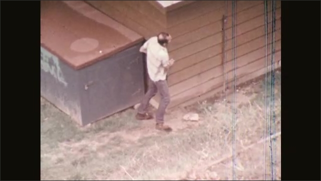 1970s: UNITED STATES: drunk man on floor throws empty bottle. Man leans against building. Man gives rides to boy in garden.