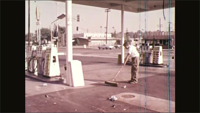 1970s: UNITED STATES: man in workshop. Man cleans garage forecourt with brush.