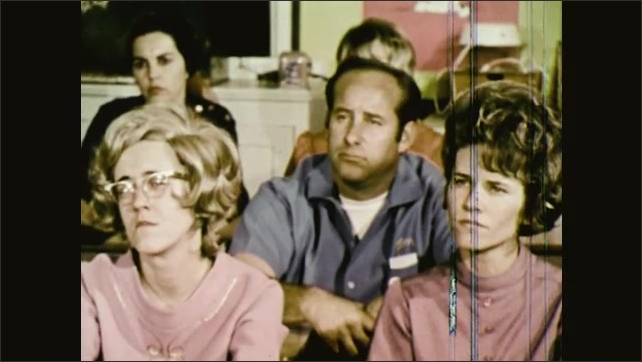 1970s: UNITED STATES: lady sits in meeting with community. Man listens to officer. Man arrives at meeting. Man raises hand.