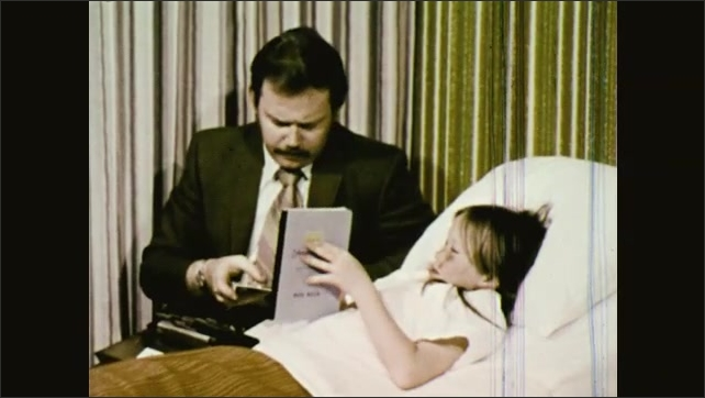 1970s: UNITED STATES: man shows photos to girl in hospital bed. Police man interviews patient