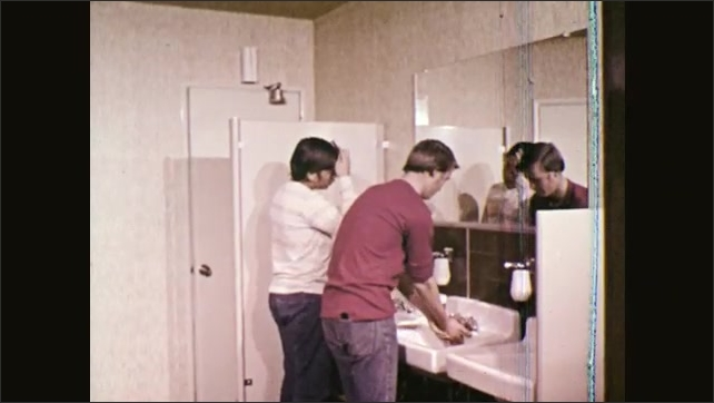 1970s: UNITED STATES: man helps girl pick up things from pavement. Men talk in bathroom. Man washes hands. Man combs hair.