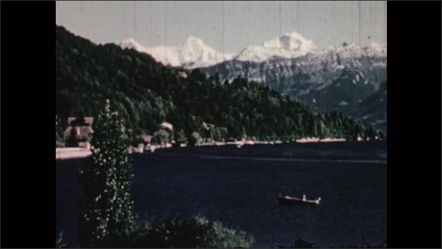 1950s: EUROPE: SWITZERLAND: snow  covered mountains. Title Credits. View across lake towards snow peaks. Blue lakes of Switzerland