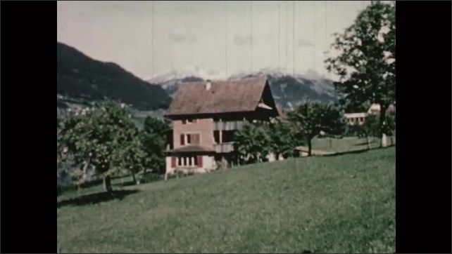 1950s: EUROPE: SWITZERLAND: boy sits on tractor. Family gather potatoes from field. View across field towards mountain. House in Swiss alps.