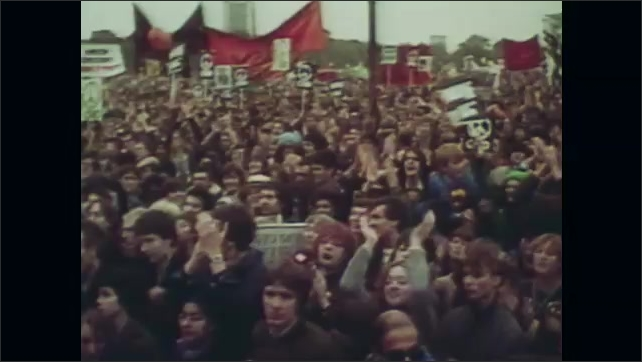 1980s: UNITED STATES: propaganda campaign. Protestors in street. People clap in crowd. People with banners.