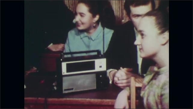 1980s: UNITED STATES: soldier in street with civilians. Soviet Union citizens listen to broadcast on radio