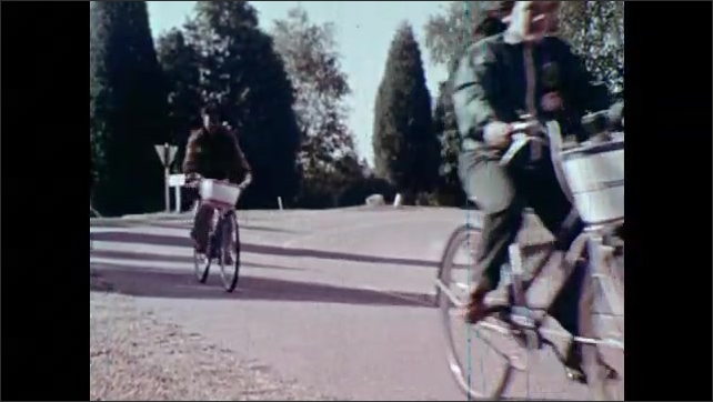 1970s: Children ride bicycles down road, through forest.