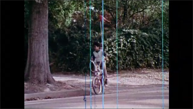 1970s: Small flag waves in the air. Children ride bicycles down path, stop, turn onto street. Children ride bikes towards stop sign, use hand signals, stop.