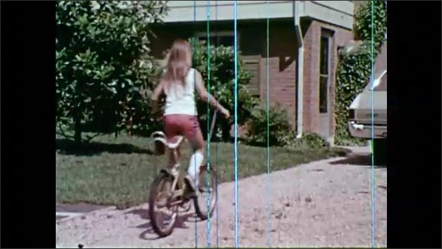 1970s: Kids walk across crosswalk. Kids on bicycles ride across intersection. Girl rides bicycle up driveway, get off bike, parks bike in grass, puts down kickstand.