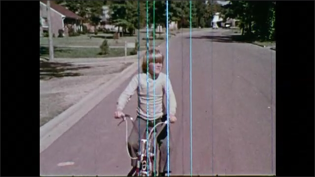 1970s: Girl looks both ways, rides bike across train tracks. Boy rides bike down street.