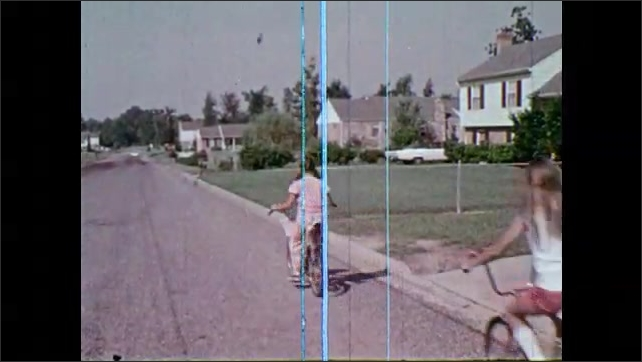 1970s: Children ride in a single file line down street. Girl rides bicycle, signals right turn.