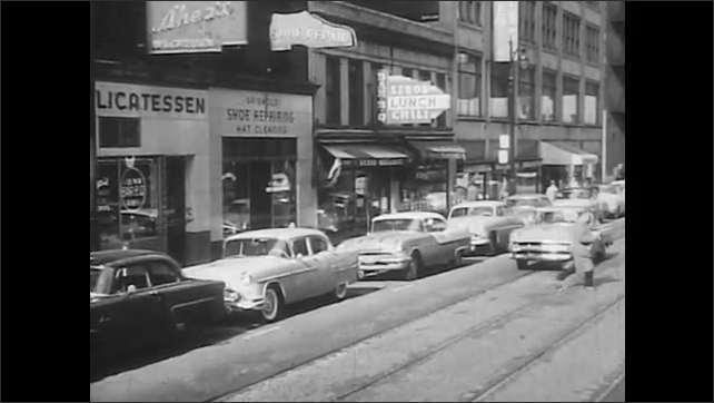 1950s: UNITED STATES: shops and parked cars on street in city. Car stops to let man cross. Car pulls on to road.