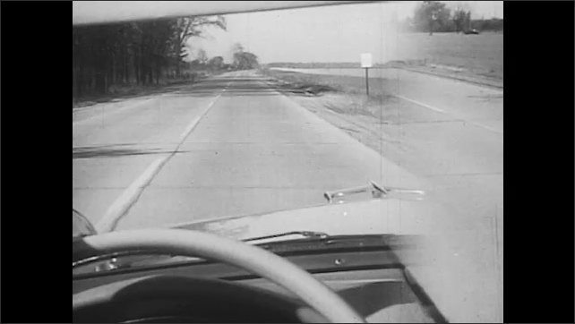 1950s: UNITED STATES: view through windscreen of car on country road. View behind man walking by side of road