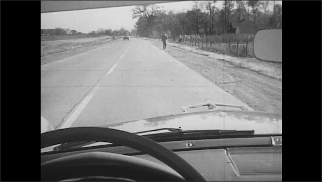 1950s: UNITED STATES: man walks along side of road without pavement. Car passes pedestrian on country road.