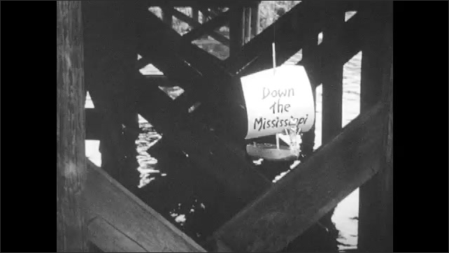 1950s: Close up of boy. Crane rises from water. Boat raises up on fishing line. Close up of boy. Boy, girl and man on pier, boy sets down boat.
