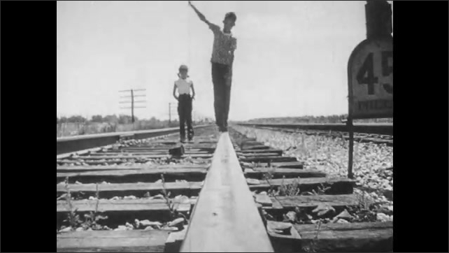 1950s: Grass blowing in wind. Tilt down grass to boat in water. Boy and girl walking on train tracks. Girl runs down hill.