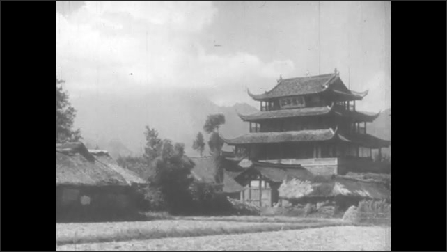 1940s: Farmers work in a field. Chinese pagoda. Small village.