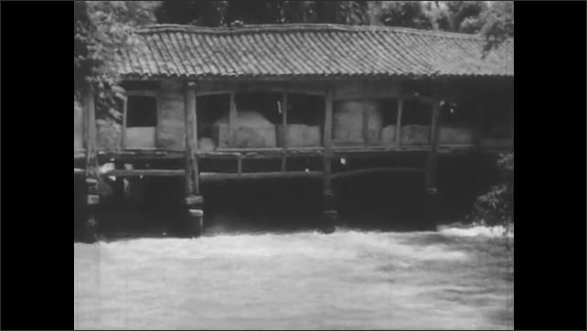 1940s: River runs through village in valley. Farmers work in field. River flows under building. Man sweeps grain around grinding stone in mill. Water wheel turns under mill.