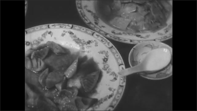1940s: Man makes chopsticks out of bamboo. Chinese family eats meal of bamboo.