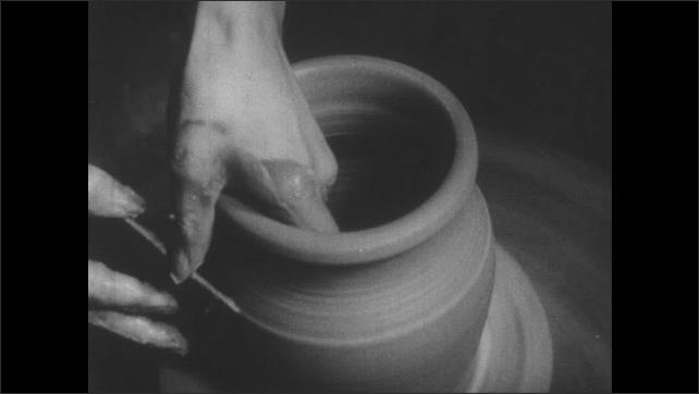 1940s: Man turns pot on pottery wheel.