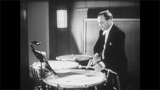 1950s: Sheet music on stand. Man plays timpani drums. Conductor waves arms and baton.