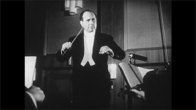 1950s: Conductor waves arms and baton before string section of orchestra.