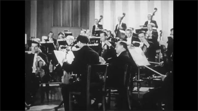 1950s: Conductor waves arms and baton. Hands flip through sheet music on stand. String section prepares instruments in orchestra. Conductor waves arms and baton.